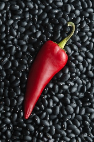 Single red chili pepper with background of dried black beans